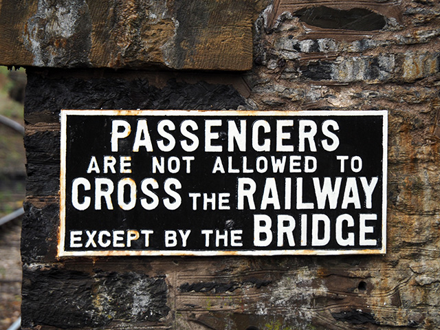 Passengers are not allowed to cross the railway except by the bridge sign.