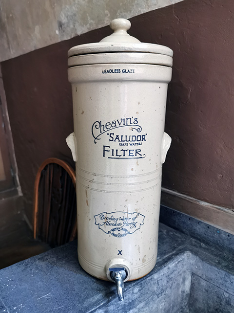 A glazed ceramic water filter marked with 'Cheavin's 'Saludor (Safe Water) Filter. Drinking water of absolute purity. British Made throughout'.