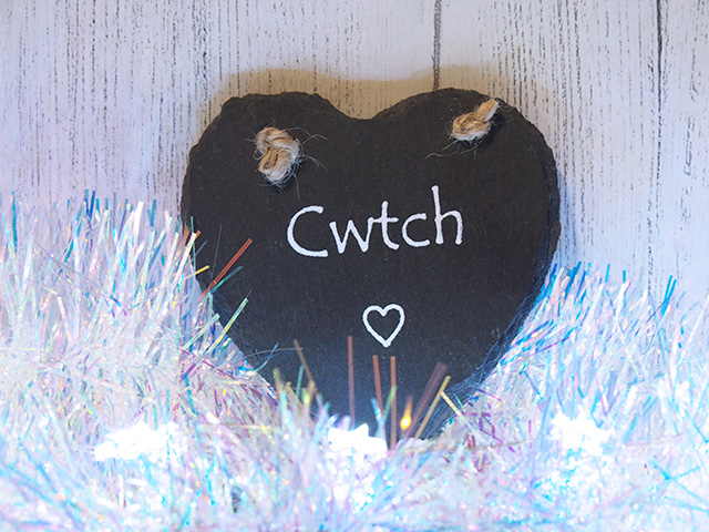 "A piece of slate in the shape of a heart with the Welsh word ""Cwtch"" on it."