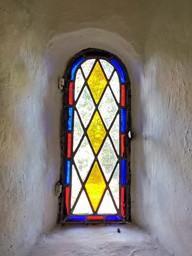 A narrow stained glass window in the church.